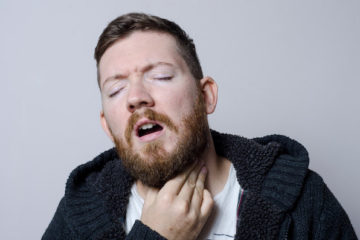 喉を痛がる男性