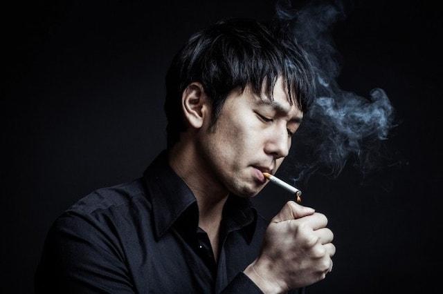 たばこに火を点ける男性